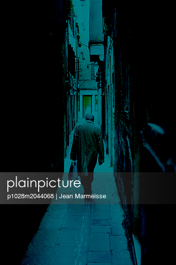 A man walking in a passage, Venice - p1028m2044068 von Jean Marmeisse