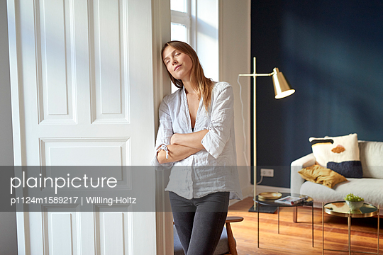 Junge Frau mit geschlossenen Augen im Wohnzimmer - p1124m1589217 von Willing-Holtz