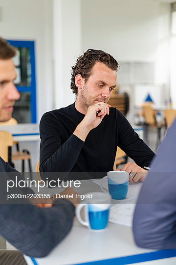 Businessman planning with colleagues during meeting - p300m2293355 by Daniel Ingold
