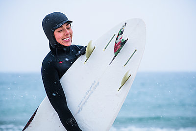 Young woman going winter surfing in snow - p1166m2177053 by Cavan Images