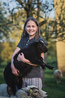 Mädchen hält schwarzes lamb - p1437m1586591 von Achim Bunz