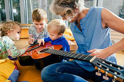 Pre-school teacher showing a guitar to children in kindergarten - p300m1537395 by Mareen Fischinger