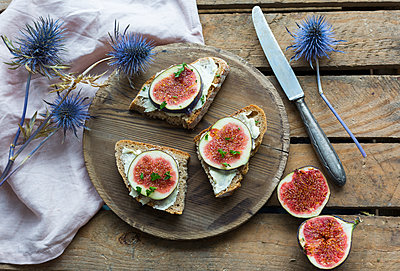 Buttered slices of bread with sliced figs on wooden plate - p300m2060301 von JLPfeifer