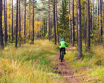 Boy cycling through forest - p312m1229037 by Mikael Svensson