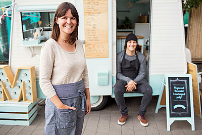 Portrait of happy female owner standing on street while colleague sitting in food truck - p426m1407083 by Maskot