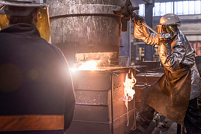 Worker pouring molten metal in foundry - p429m768972f by Monty Rakusen