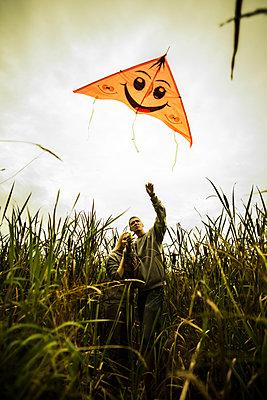 Caucasian couple flying kite in rural field - p555m1418709 by Aleksander Rubtsov