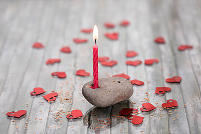 Stone as candleholder among red hearts - p788m1220757 by Lisa Krechting