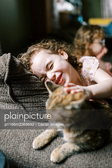 Little girl playing with her cat on the couch in the living room - p1166m2269692 by Cavan Images
