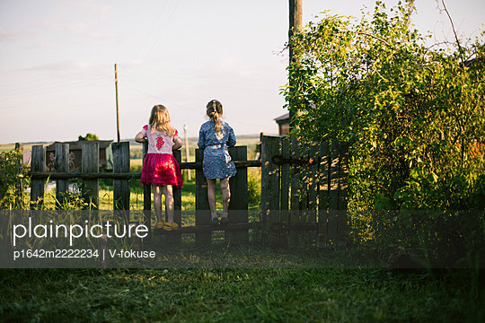 Two girls looking over garden fence - p1642m2222234 by V-fokuse