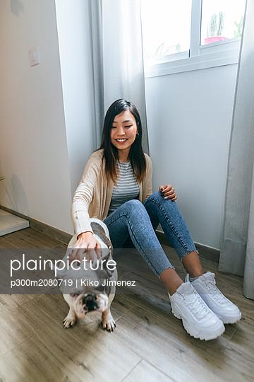 Young woman sitting on ground, stroking pug - p300m2080719 by Kiko Jimenez