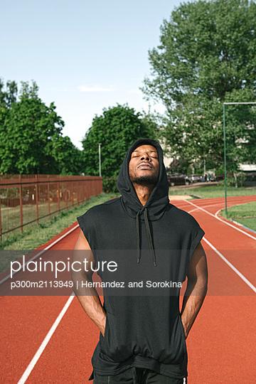 Portrait of sportsman wearing black hoodie shirt - p300m2113949 von Hernandez and Sorokina