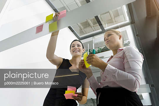 Female colleagues sticking adhesive notes on glass wall while standing in office - p300m2225061 by Buero Monaco