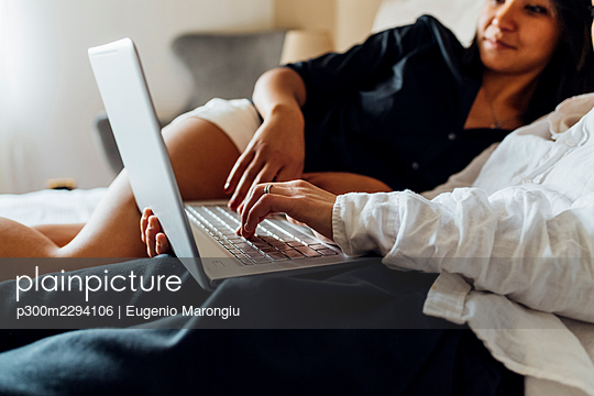 Young girlfriends using laptop in bedroom at home - p300m2294106 by Eugenio Marongiu
