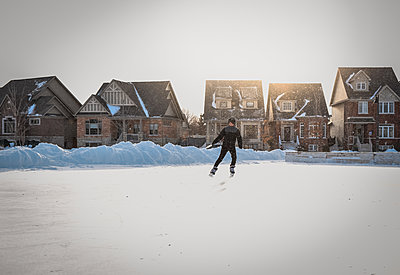 Teenage boy skating alone on an outdoor neighbourhood ice rink. - p1166m2095872 by Cavan Images