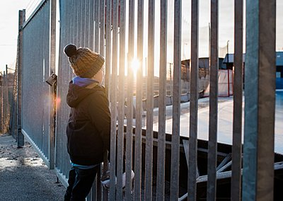 young boy looking out at an ice rink at sunset with his skates - p1166m2157416 by Cavan Images
