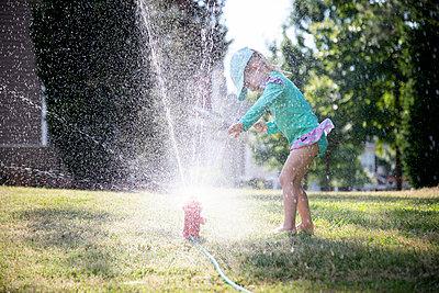 Portrait of a young girl playing in a backyard sprinkler - p1480m2148166 by Brian W. Downs