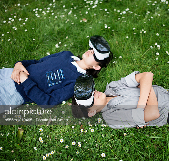 Mixed Race brother and sister laying in grass wearing virtual reality goggles - p555m1219465 by Donald Iain Smith