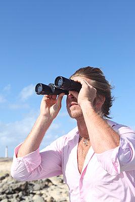 Man holding binoculars - p045m902739 by Jasmin Sander