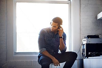 Man listening music through headphones at home - p1166m1150852 by Cavan Images
