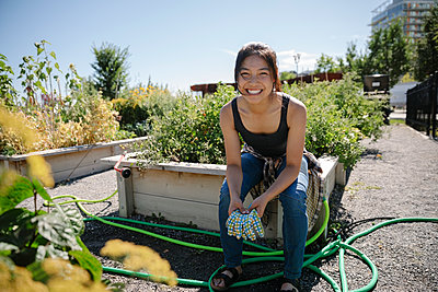 Portrait happy young woman gardening in sunny community garden - p1192m2130070 by Hero Images