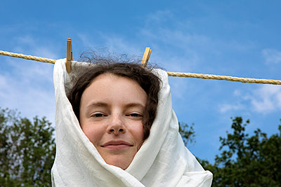 Portrait of smiling young woman wrapped in white cloth haning on clothesline - p300m2156644 by Petra Stockhausen