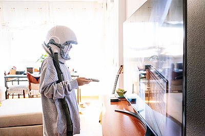 Boy wearing space helmet watching TV while standing at home - p300m2221002 by Jose Luis CARRASCOSA