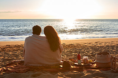 Young couple covered in blanket looking at view while sitting on beach - p300m2243441 by Veam