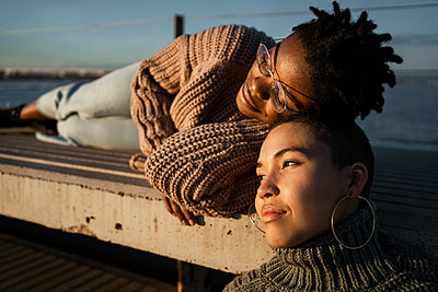 Female friends resting on bench during sunset - p300m2244023 by Rafa Cortés