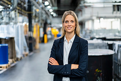 Young businesswoman with arms crossed standing at industry - p300m2298929 by Daniel Ingold