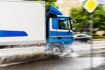 Lorry splashing water on road - p312m1103993f by Mikael Svensson
