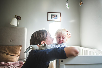 Father consoling crying blond baby boy in crib with tender love at home - p426m2159787 by Maskot
