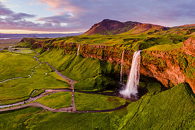 Aerial drone view of Seljalandsfoss waterfall at sunset, Iceland - p651m2007284 by Matteo Colombo photography