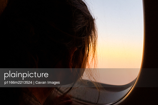 Little girl looking out airplane window during flight - p1166m2213524 by Cavan Images