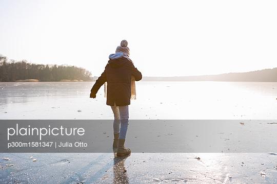 Germany, Brandenburg, Lake Straussee, back view of a girl walking on frozen lake - p300m1581347 von Julia Otto