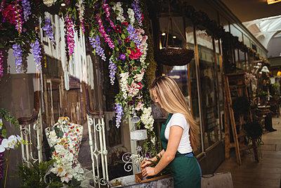 Female florist arranging flowers in wooden box - p1315m1199871 by Wavebreak