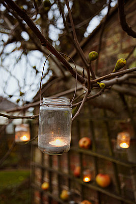 Tealights in jam jars hanging from trees light a night garden - p3493269 by Jonathan Birch