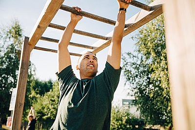 Male athlete hanging on monkey bar in park on sunny day - p426m2270612 by Maskot