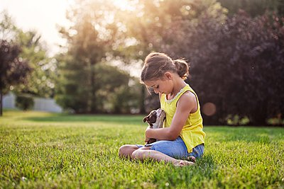 Girl sitting on grass holding Boston Terrier puppy - p429m1084669 by Rebecca Nelson