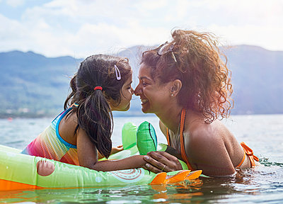 Mother rubbing noses with daughter on inflatable frog in lake - p429m2091725 by Sverre Haugland