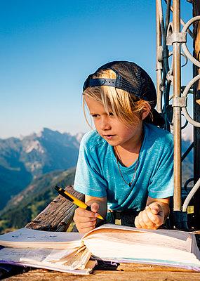 Boy enjoying view and writing notes on peak, Bludenz, Vorarlberg, Austria - p429m2153047 by ©JFCreatives