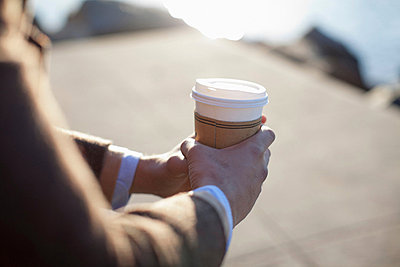 Close up of man holding cup of coffee - p924m757048f by Chad Springer