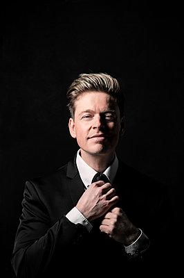 Businessman tying his tie, portrait - p947m2257932 by Cristopher Civitillo