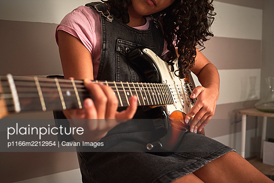 Close-up of a girl playing the electric guitar - p1166m2212954 by Cavan Images