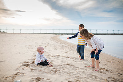 Full length of siblings enjoying at beach against cloudy sky - p1166m1474076 by Cavan Images