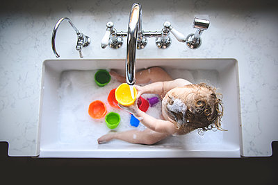 High angle view of naked girl playing with colorful toys while bathing in sink at home - p1166m2033919 by Cavan Images