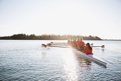 Rowing team in scull on sunny river - p1192m1016588f by Hero Images