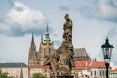 Statues on Charles Bridge with the St. Vitus Cathedral in the background - p1332m2205612 by Tamboly
