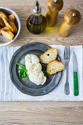 Mozzarella braid, basil and bread on plate - p300m2029116 by Giorgio Fochesato