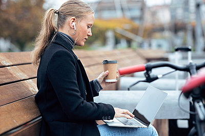 Woman using laptop while holding coffee cup by bicycle - p300m2256033 by Josep Suria